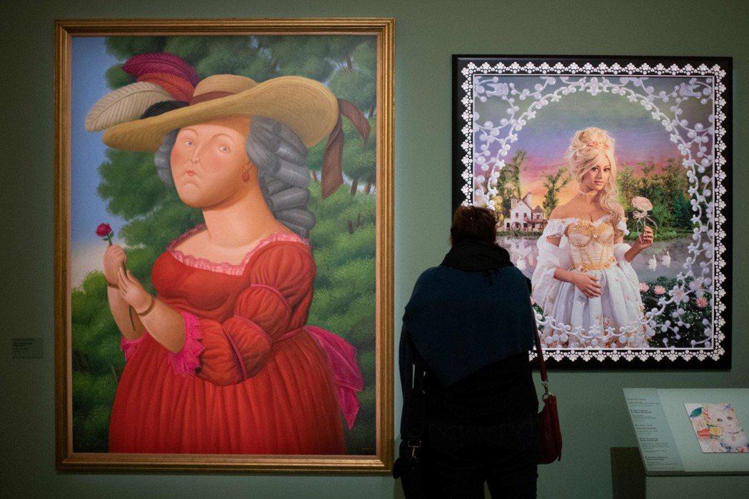 一名女子正欣賞各種風格的瑪麗王后肖像。(法新社)