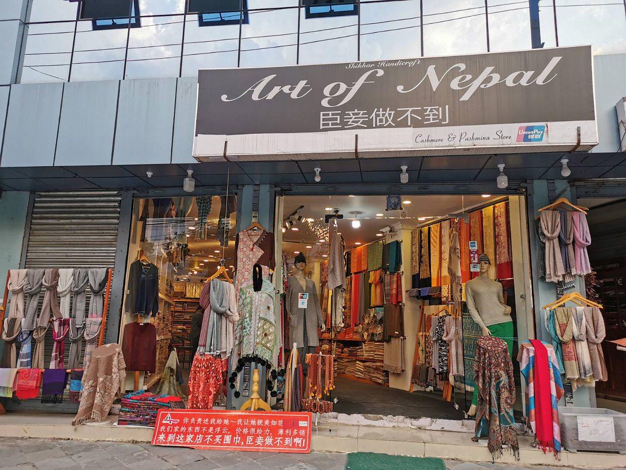 位在尼泊爾第2大城市波卡拉(Pokhara)街上,販售傳統服飾的店家在招牌寫上中...