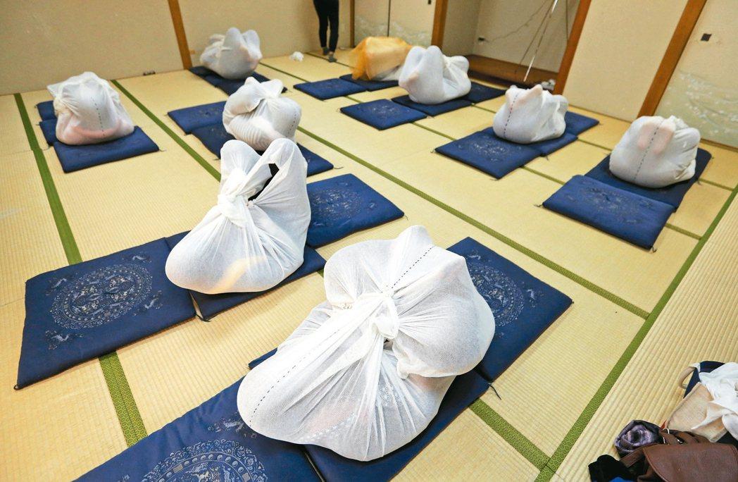 「成人捲」(Otonamaki)是日本為上班族提供的減壓課程,學員用白布把自己包...