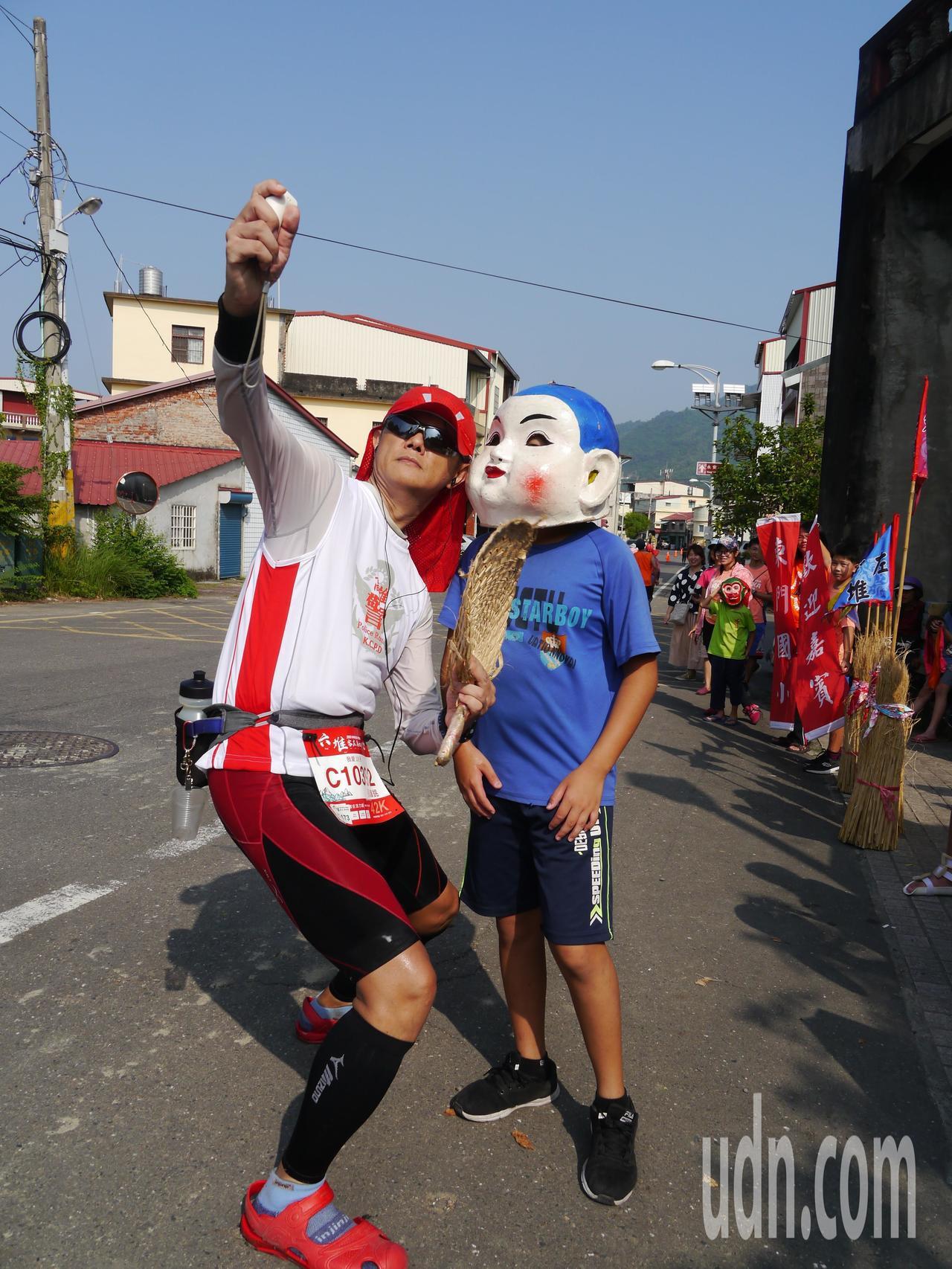 美濃東門國小客家獅成員替選手加油,跑者主動要求拍照留念。記者徐白櫻/攝影