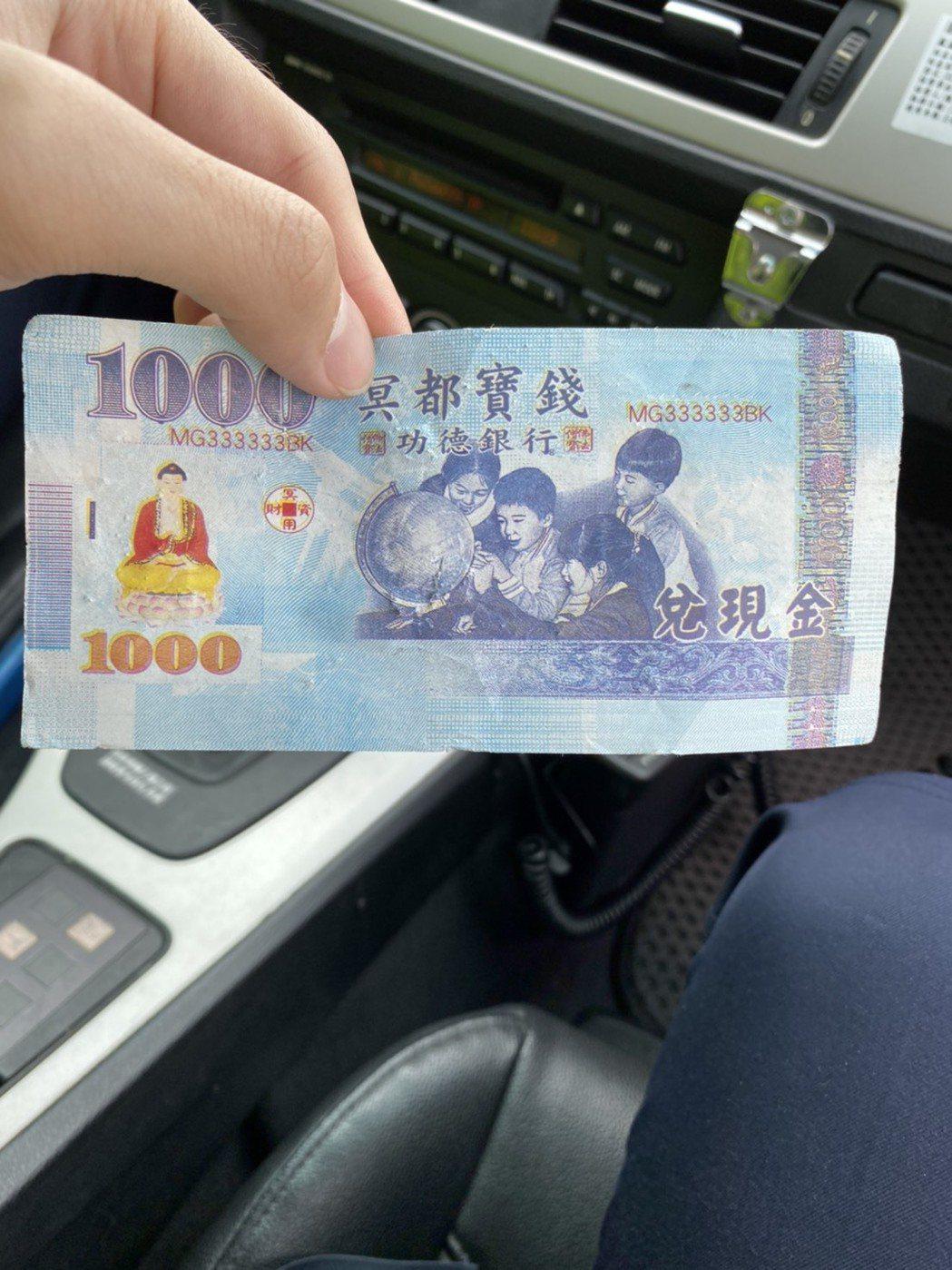 昨日上午國道3號由龍潭交流道傳出疑似大量鈔票散落,國道警察到場後撿到千元冥鈔。圖...