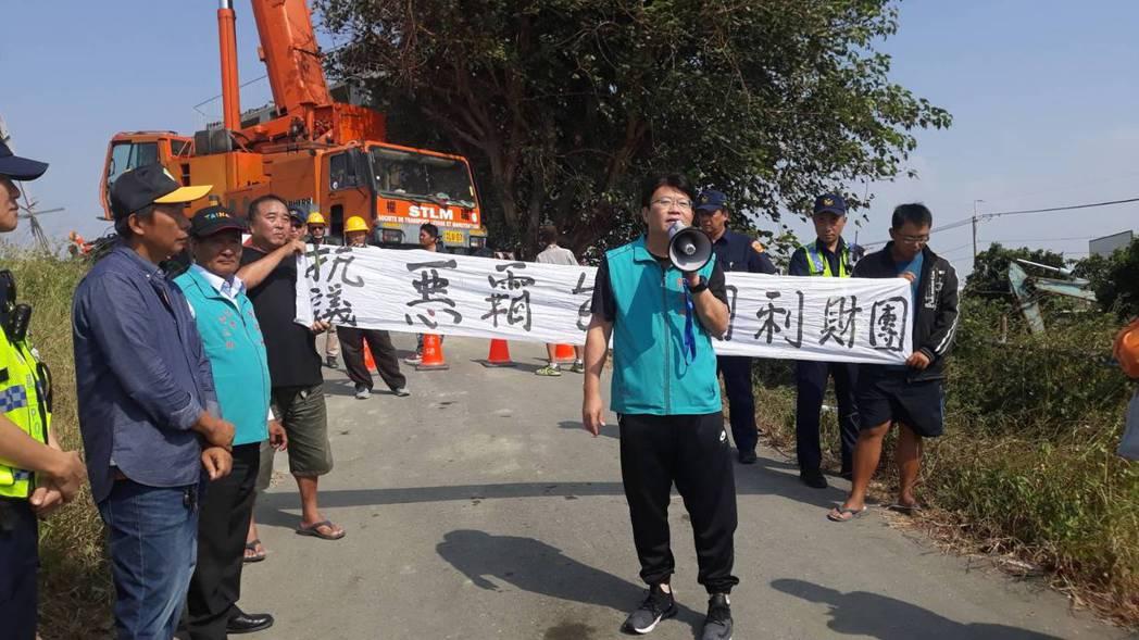 不滿台電公司在國聖橋南岸興建高壓電塔,台南市議員陳昆和(中)率領多人前往拉布條抗...