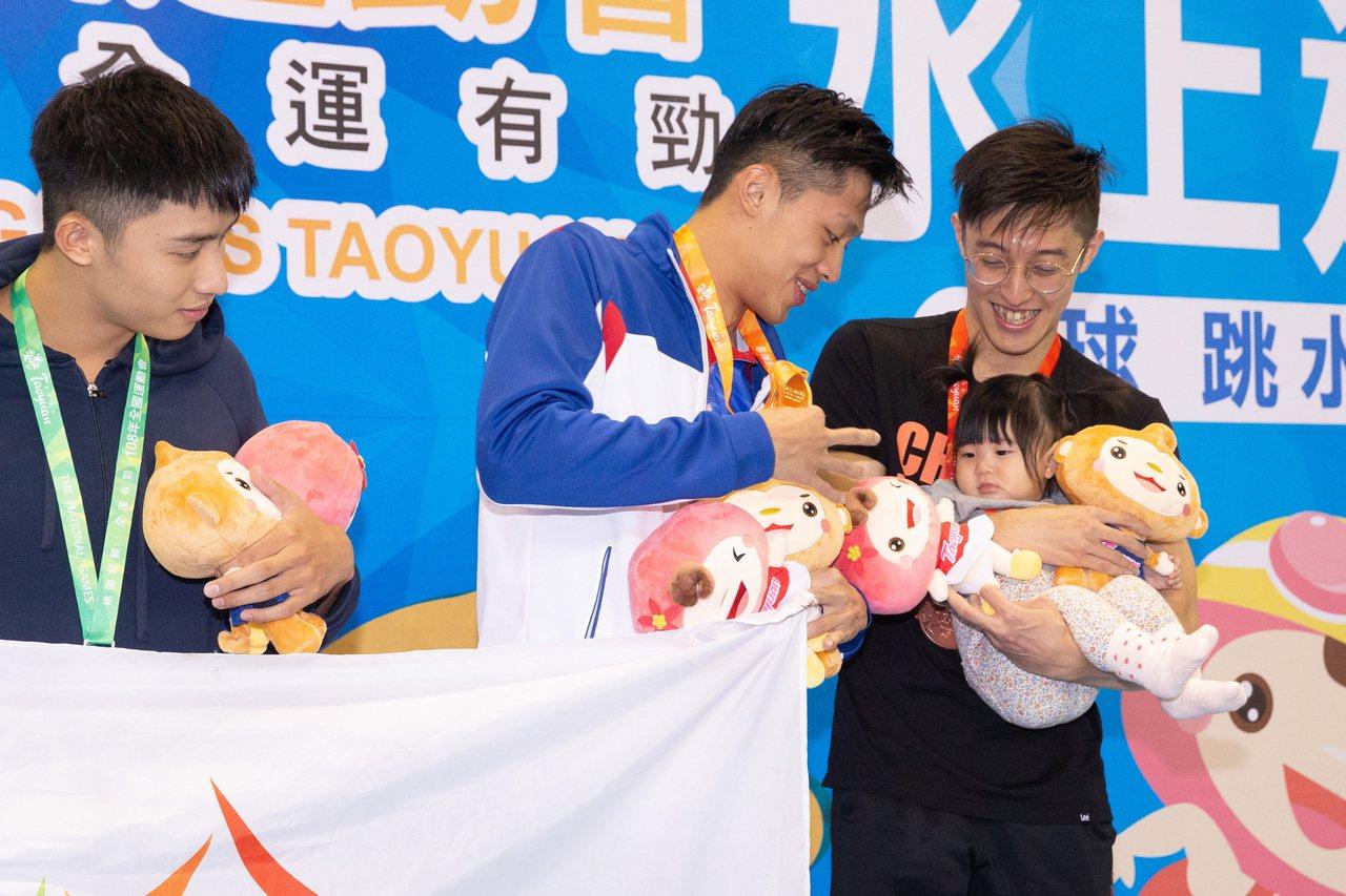 李炫諺(右一)抱著女兒站上男子200公尺蛙式頒獎台。記者季相儒/攝影