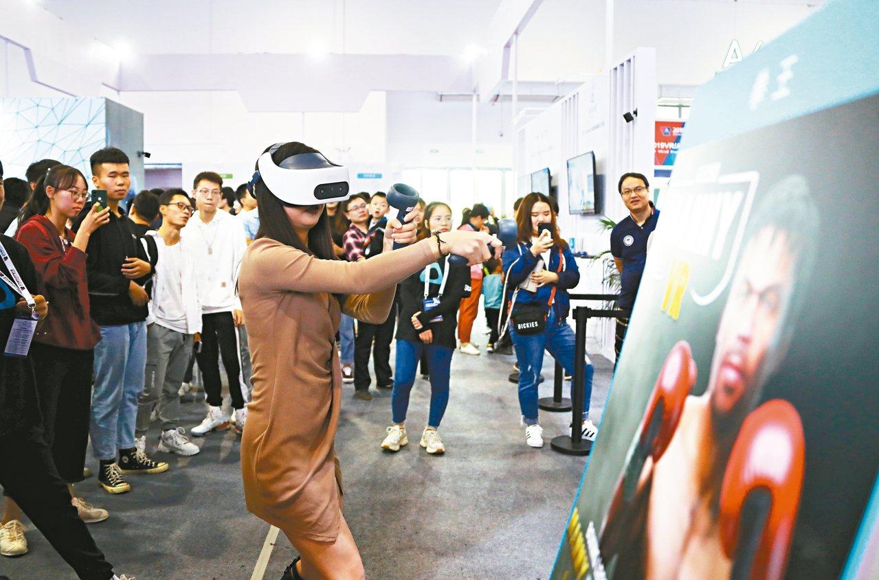 觀眾頭戴VR設備體驗「VR拳擊」,感受真實的拳擊比賽。 中新社