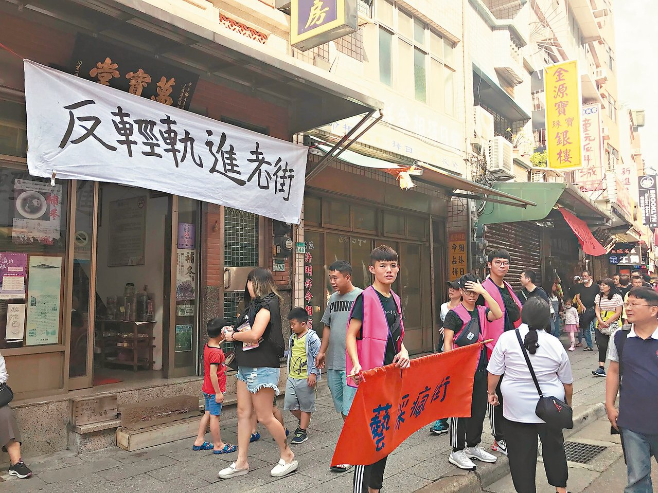 淡水老街部分店家昨天趁著遊行踩街時,在店面掛起「反對輕軌進入老街」等布條。 記者...