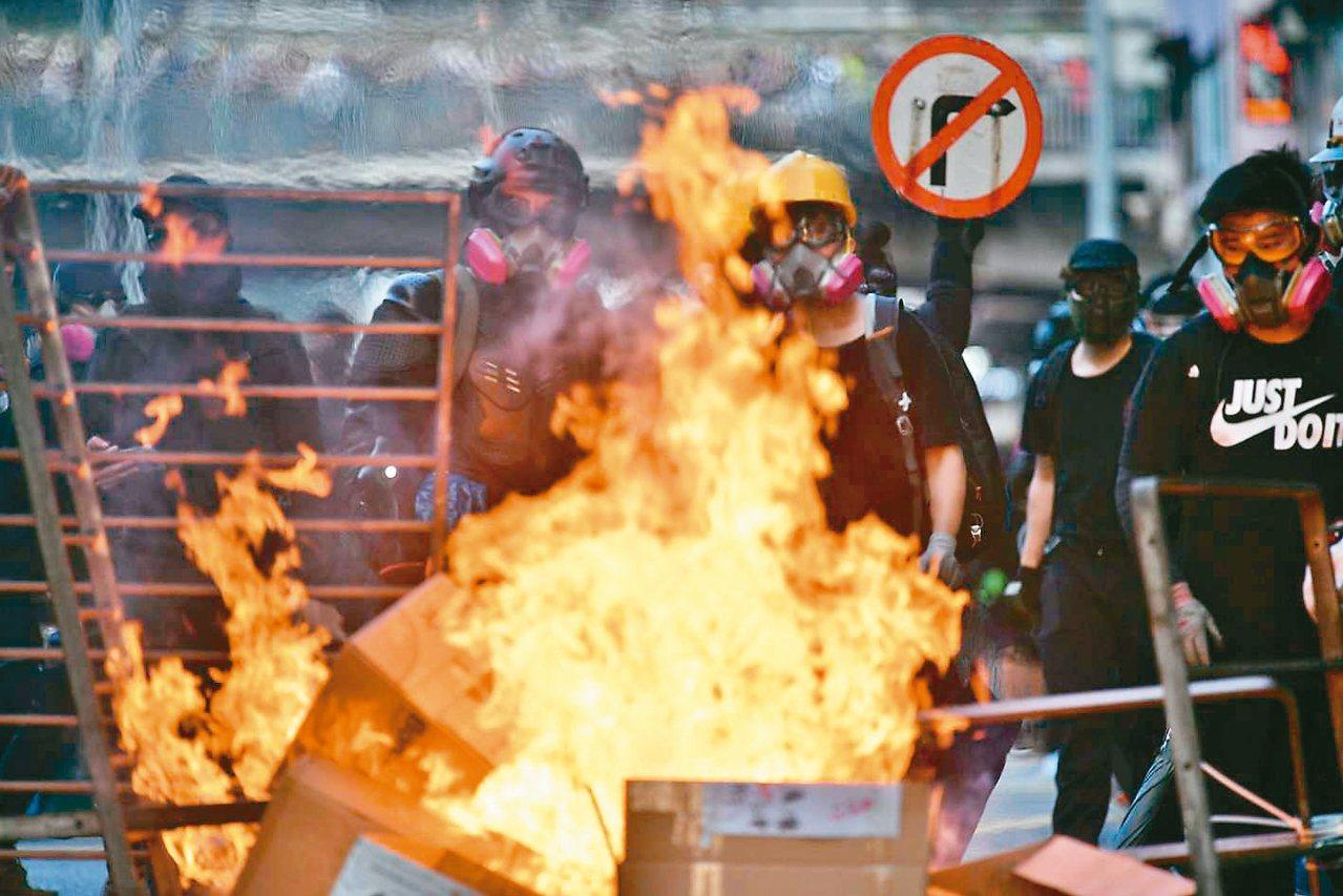 香港九龍遊行,再爆警民衝突,部分示威者在多處路段縱火。 (法新社)