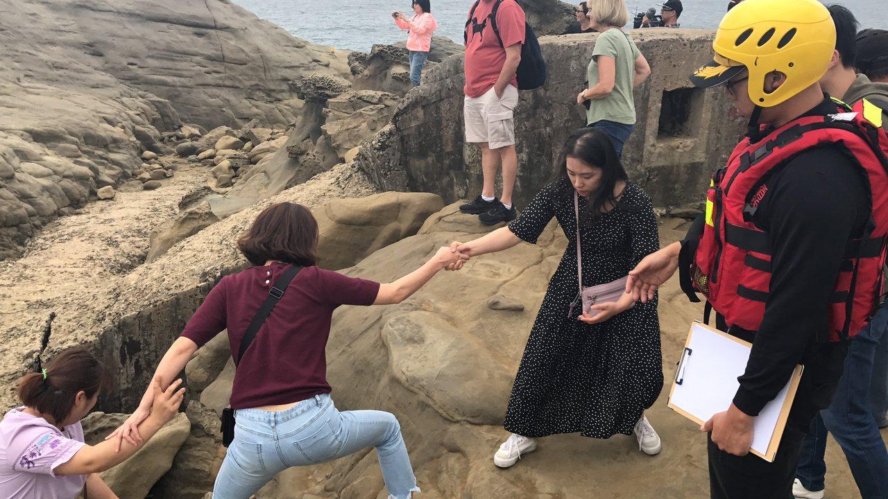 今天下午象鼻岩湧入許多遊客,消防人員制止遊客爬上象鼻岩。記者吳淑君/攝影
