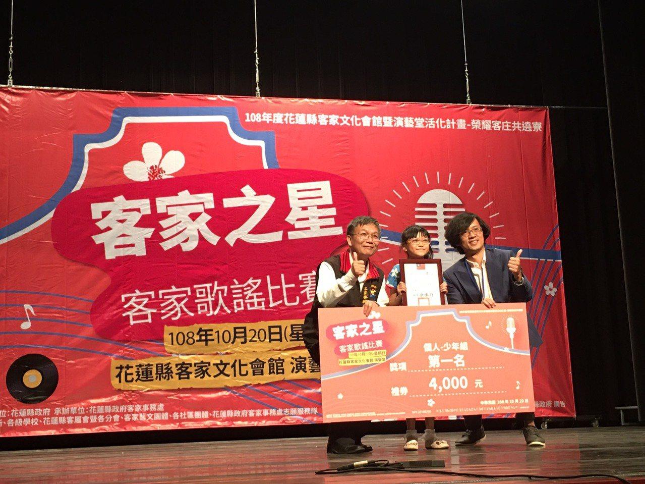 客家事務處長彭偉族(左)頒發客家歌謠比賽少年組冠軍給10歲邱詒玲(中)、指導老師...