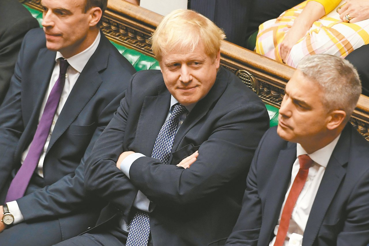 英國首相強生(中)要求國會下議院廿一日再度表決脫歐協議,但遭議長以不符議事規則為...