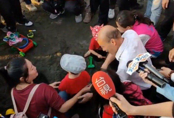 韓國瑜日前想和小孩子玩沙,卻碰一鼻子灰。 圖/截取自「土包子志工團」臉書