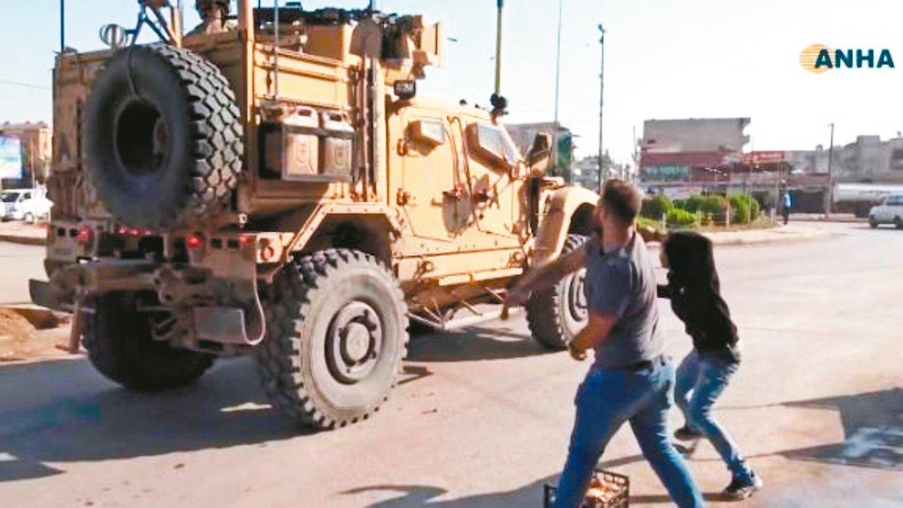 美軍車隊21日撤離敘北城鎮時,沿途遭庫德族丟馬鈴薯和其他腐爛的蔬菜水果。 圖/截...