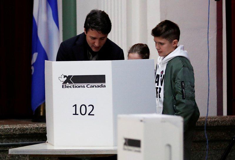 加拿大21日舉行大選,投票站關閉後,加拿大廣播公司預測,總理杜魯多(左)領導的自由黨將可組成少數政府。圖為杜魯多在家人陪同下投票。路透