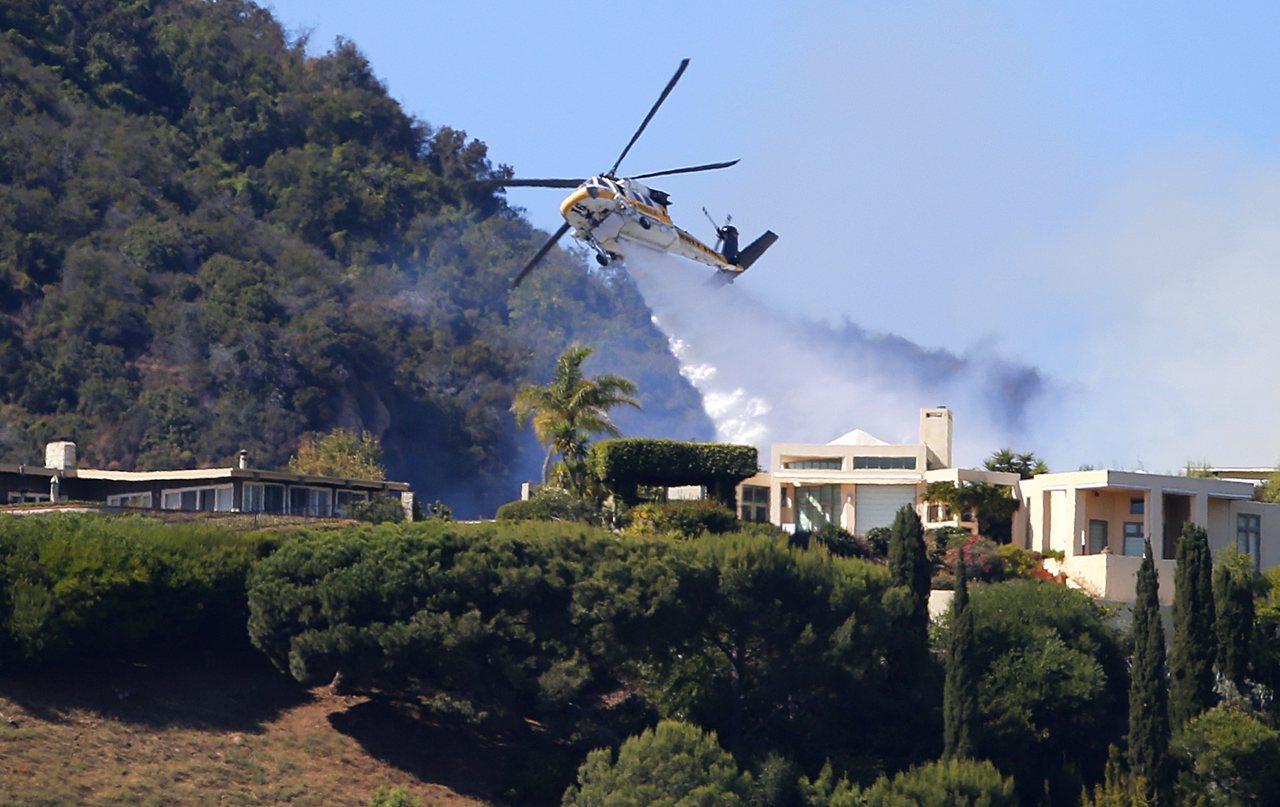 美國洛杉磯西部21日早上驚傳野火,消防局獲報立即出動300名消防人員滅火,並派出...