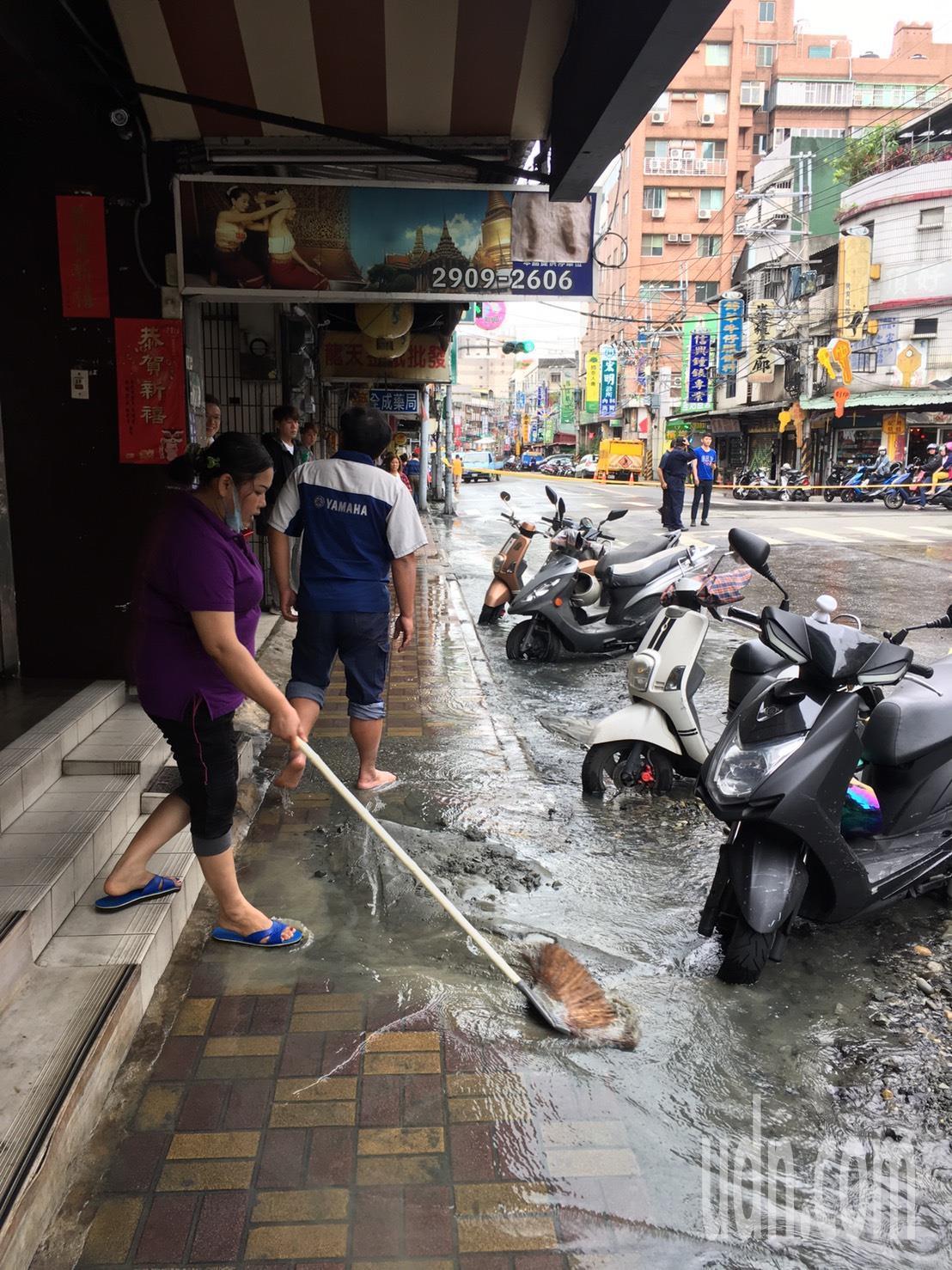 自來水夾帶泥沙沖進路旁商店,店家連忙清理善後。記者陳弘逸/攝影