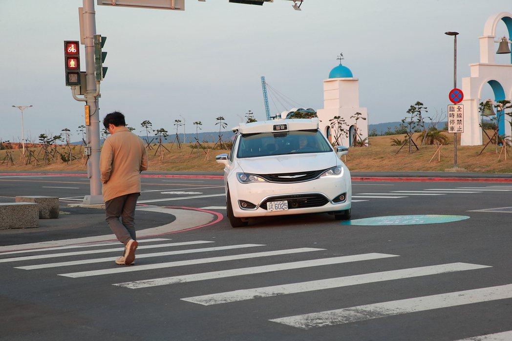 在無號誌燈號的馬路口,工研院自駕車遇到行人穿越馬路,會減速剎車,禮讓行人先行。記...