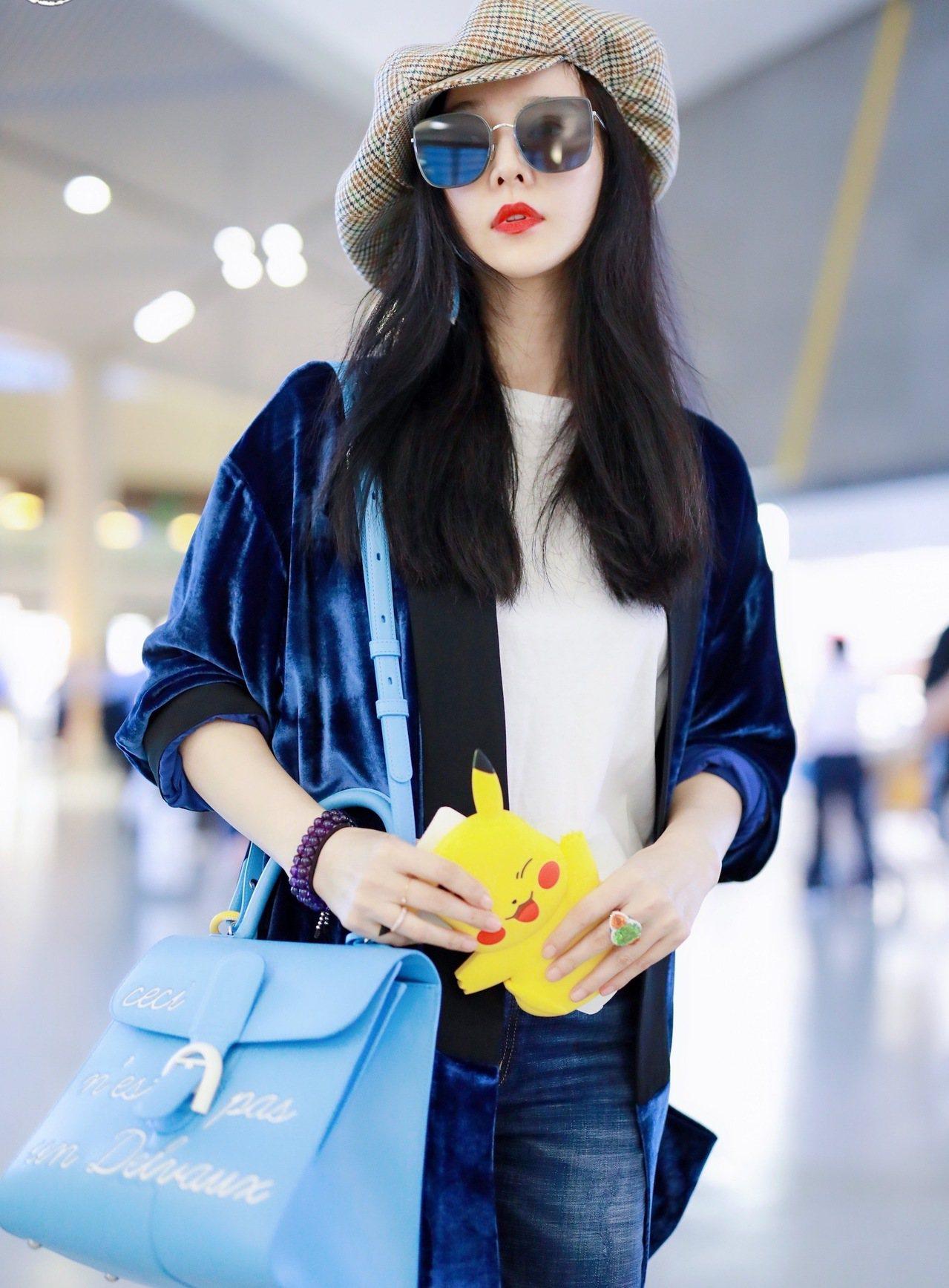 范冰冰在北京機場現身,以招牌大紅唇搭配DELVAUX Magritte系列天堂藍...