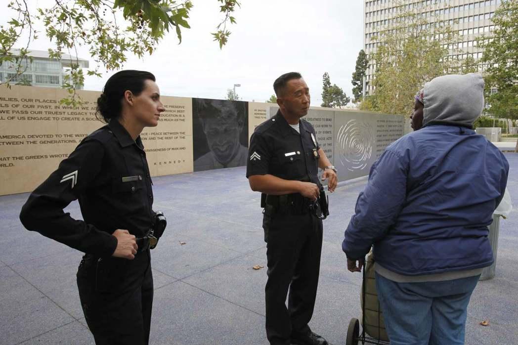 兩名洛杉磯警局警員在韓國城內向遊民問話。 (路透)