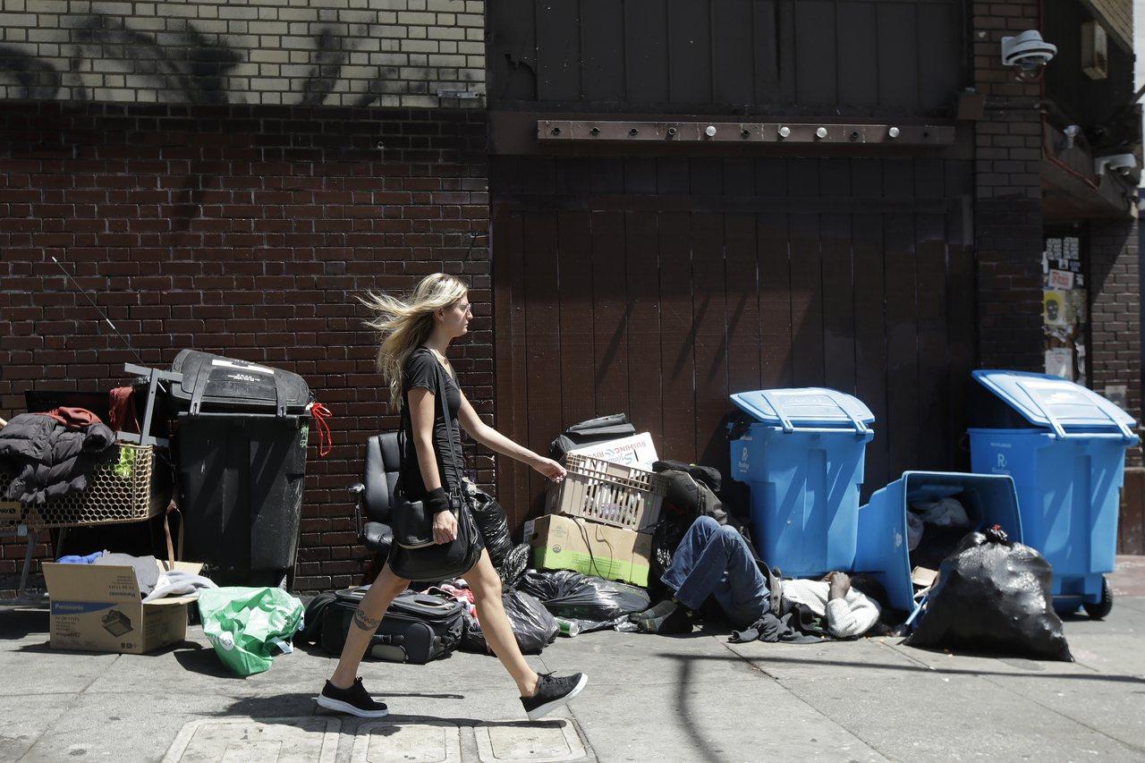 遊民近年來成為嚴重的美國社會問題。圖為一名衣著光鮮的女孩走過舊金山街頭一名睡在垃...