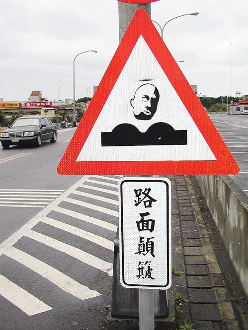 淡水油車口停車場旁交通標誌「警告人車注意路面顛簸」,被畫上一顆人頭,引人注目。 ...