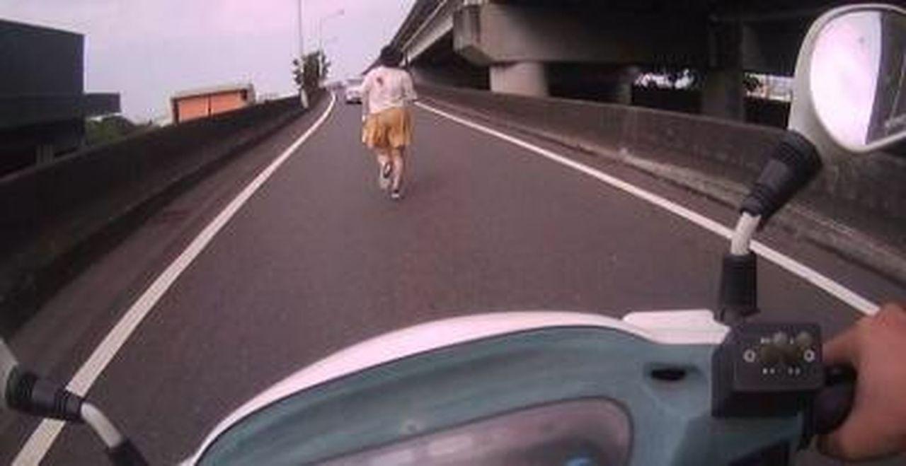 警員鄭博文獲報後,冒險騎警用機車上匝道鳴笛按喇叭,警示輛注意前方路況,不要撞到這...