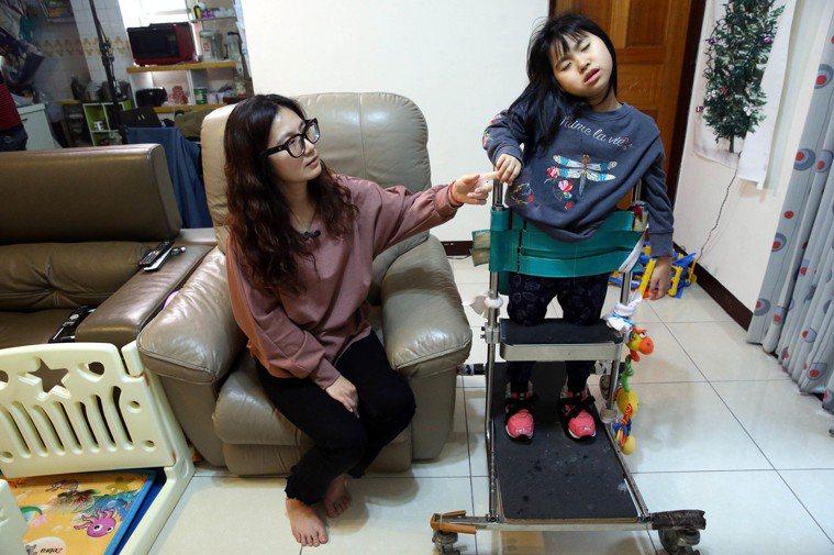 媽媽鄭淑娟(左)每天陪女兒澄寗(右)練習站在站立架上,訓練肌肉張力,雖然很辛苦,...