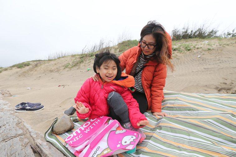 鄭淑娟(右)帶著女兒澄寗(左)坐在海邊吹海風,澄寗開心到不斷張口微笑。記者許正宏...
