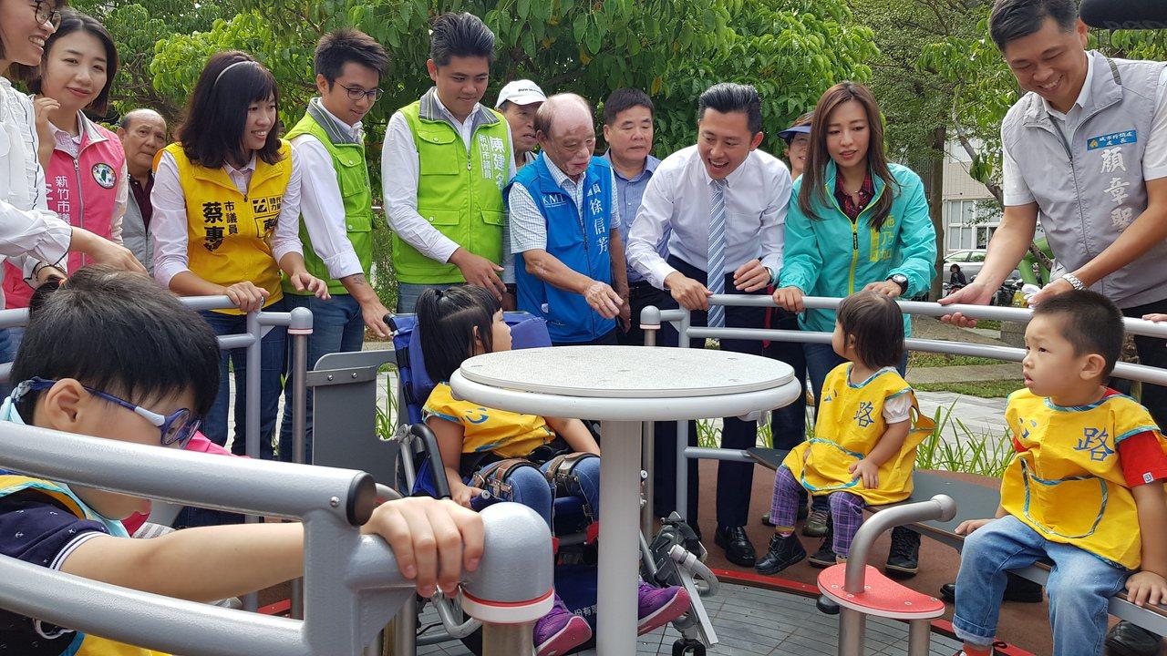 新竹市長林智堅等人為心路基金會兒童日間服務中心的小朋友轉動無障礙旋轉盤遊具。記者...
