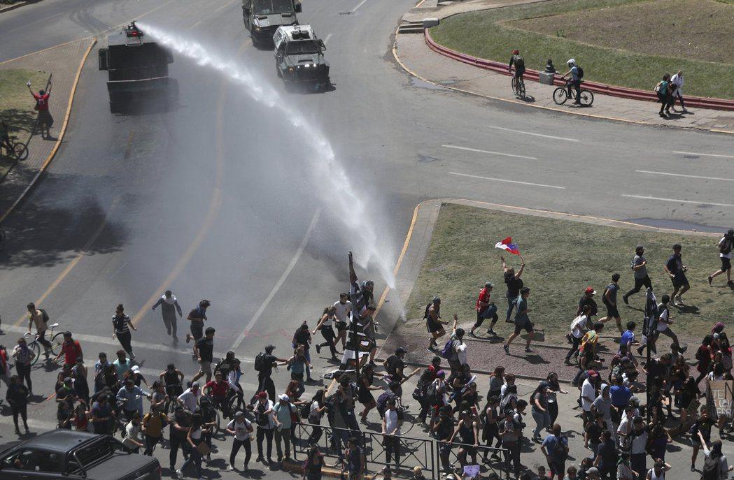 智利警察22日在聖地牙哥以水車試圖驅散示威者。(美聯社)
