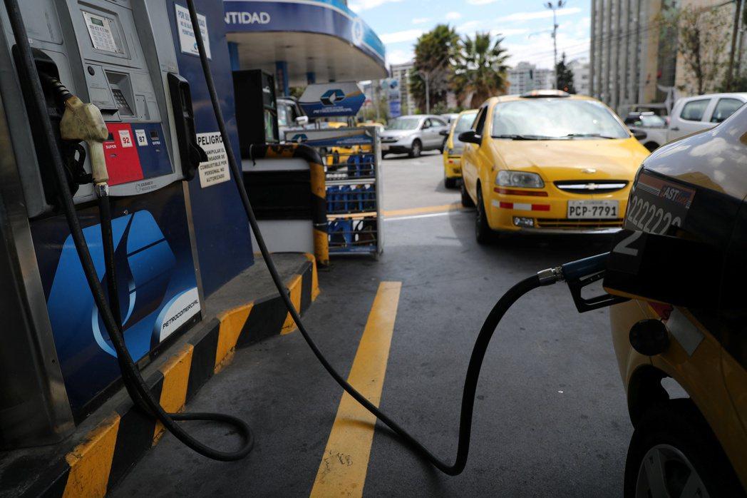 厄瓜多政府打算取消補貼調漲油價,引發民怨。圖為在首都基多排隊加油的車輛。(路透)