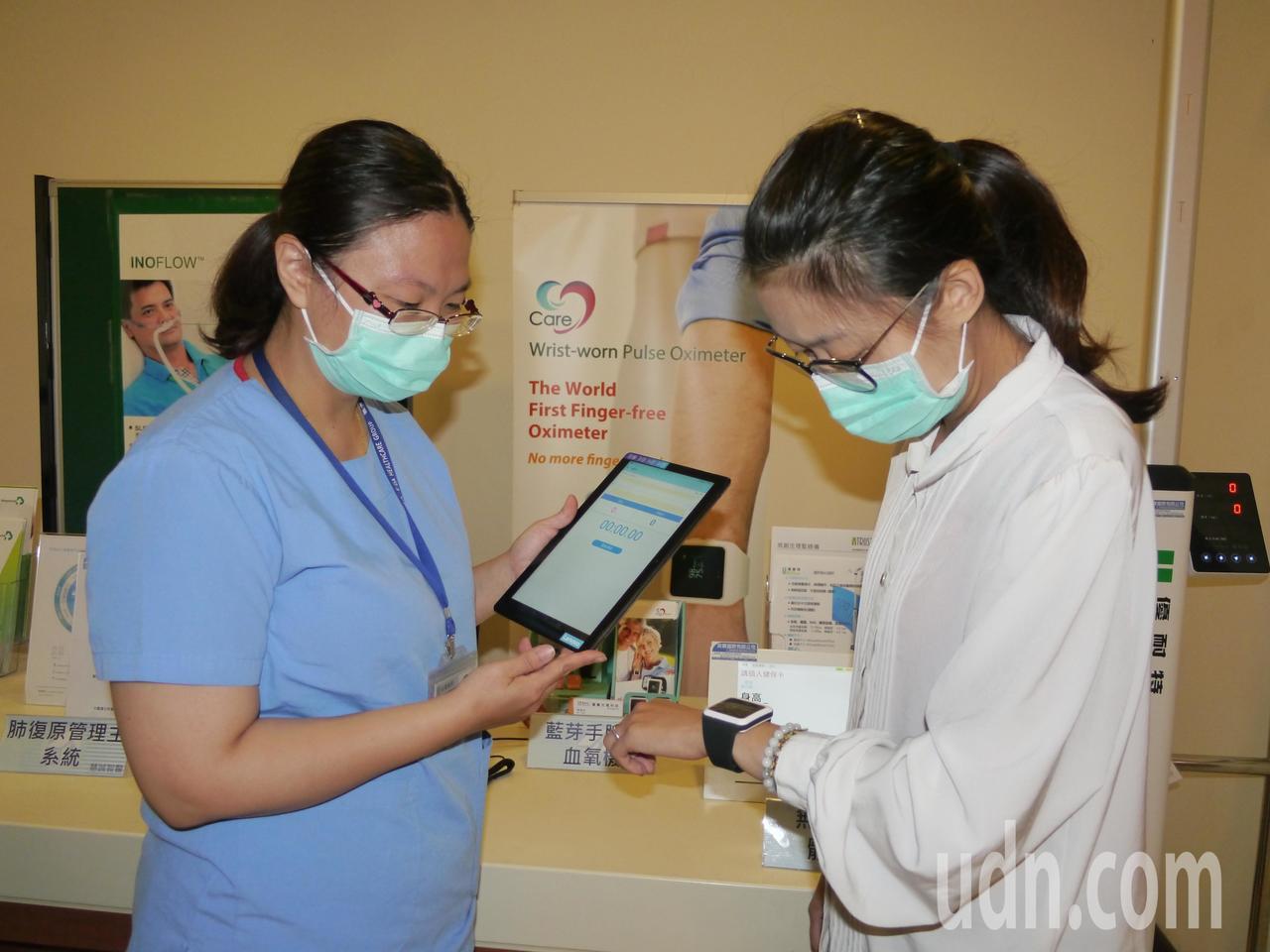護理人員示範手腕式血氧機用法,病患(右)戴在手上,醫護人員(左)即可透過手中平板...