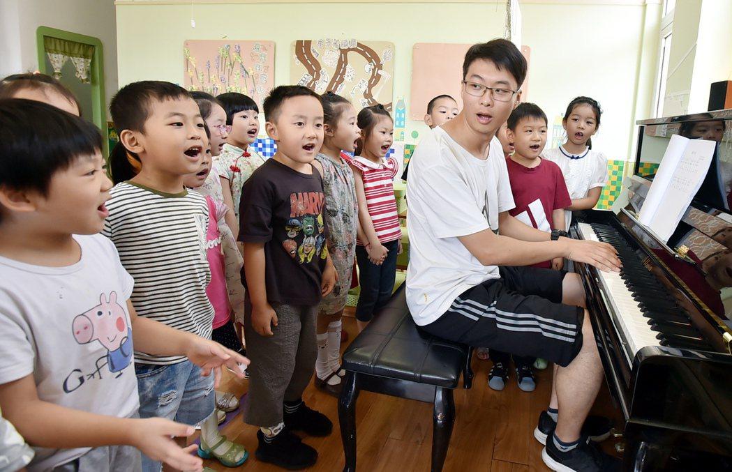 為了培養男孩的陽剛氣質,大陸許多地方這幾年刻意培育幼兒園男教師。 (新華社)