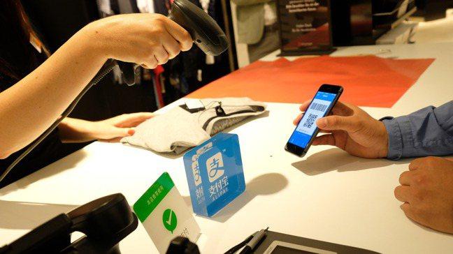 「支付寶」與「微信支付」是中國行動支付兩大巨人。圖/新華社
