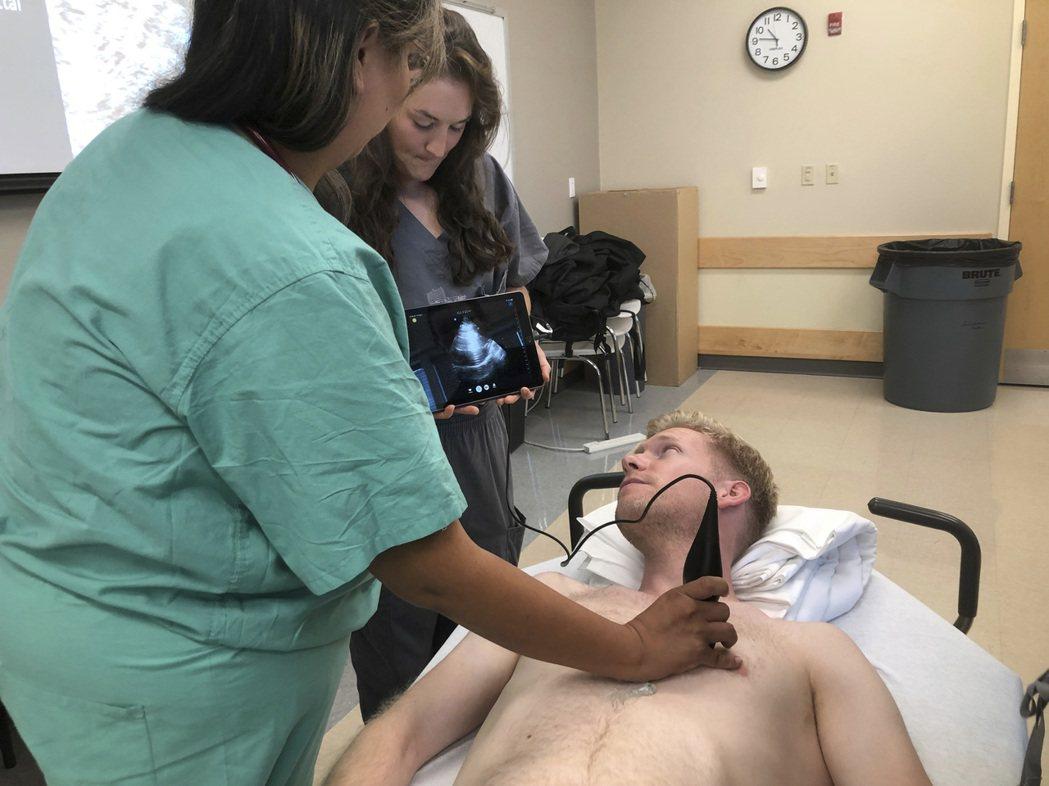 印第安納大學醫學院學生在同學身上練習使用蝴蝶iQ手持超音波裝置。 (美聯社)