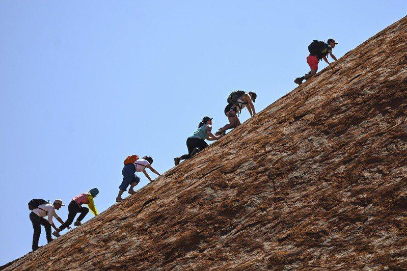 登山客25日搶爬烏魯魯巨岩。美聯社