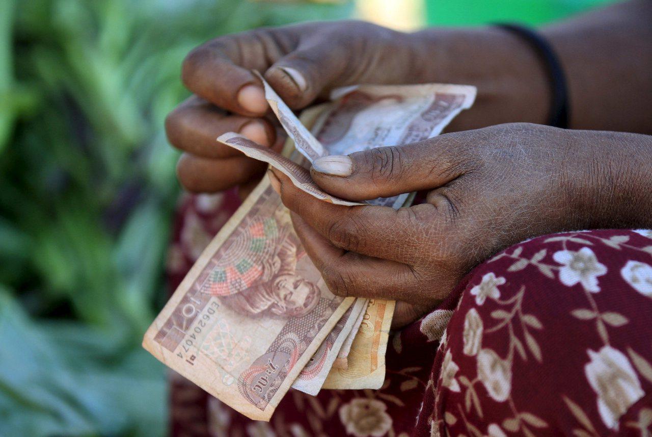 衣索比亞貧窮人口比率高,圖為衣國民眾數錢畫面。路透