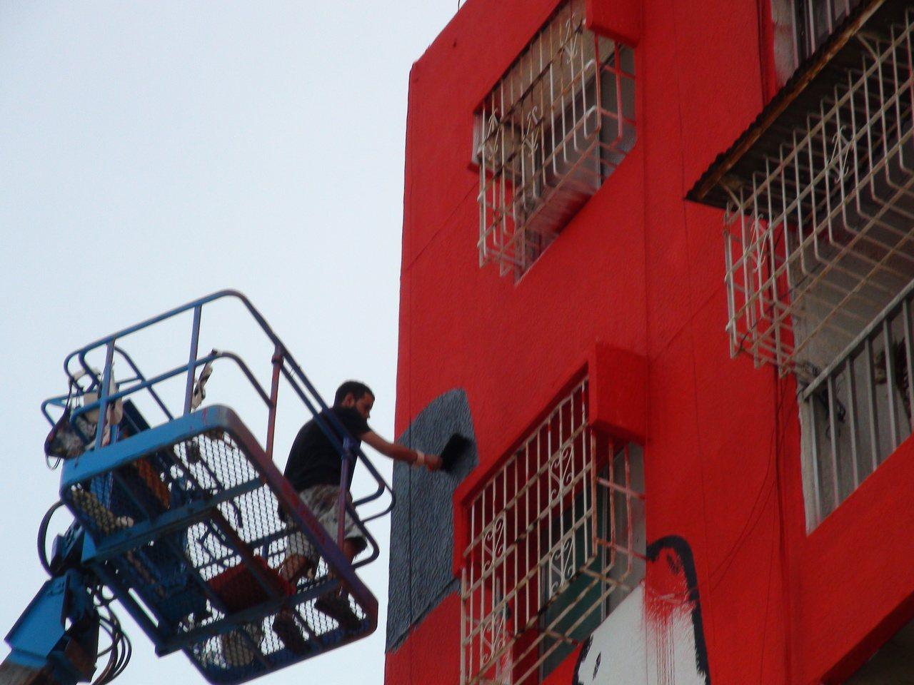 高雄市衛武營彩繪村有不少外籍畫家在高樓作畫。記者謝梅芬/攝影