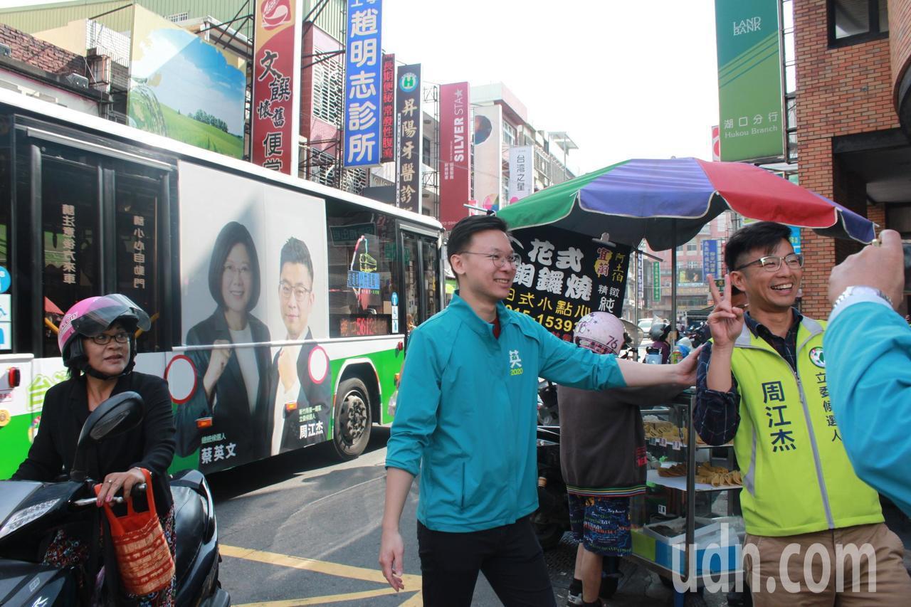 民進黨新竹縣立委第一選區參選人周江杰今天一早看到公車上的選舉廣告,立刻合影留念。...