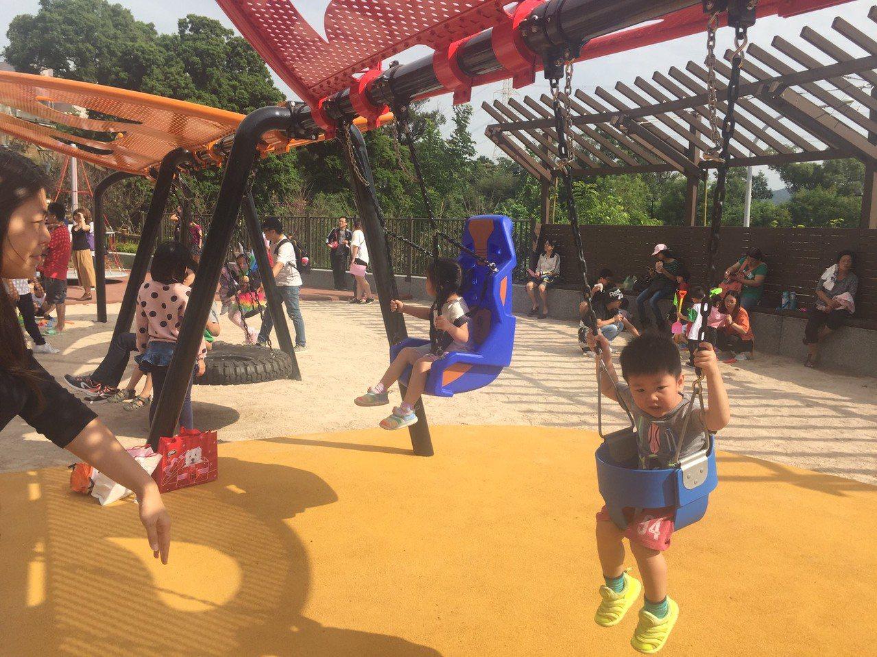 永吉公園第三期以「花朵樂園」為主題,打造花朵造型的木平台、錐形攀爬網、蝴蝶鞦韆及...