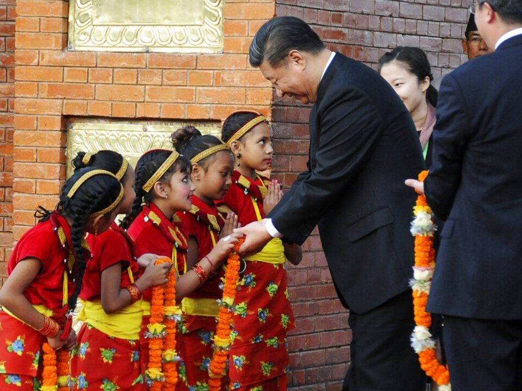 習近平訪問尼泊爾時接受當地兒童獻花。 (美聯社)