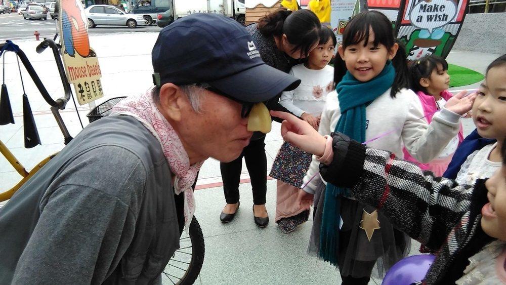 林將戴起黑框大鼻的小丑裝扮,沿街叫賣老鼠貝果,逗孩子們開心。 圖/林將提供