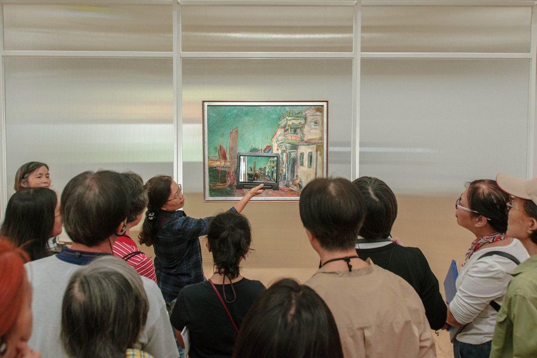 展覽現場,館員為來賓講解結合最新AR技術的本館典藏品。 高美館/提供