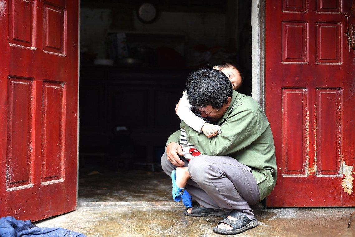 「他是個好人,只是想多分擔家計...」圖為一位越南農村的老父親,抱著自己年幼的孫...