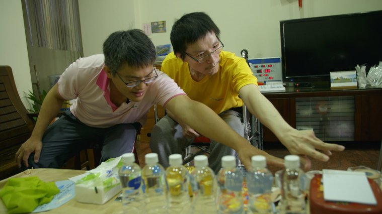 張國寬(右)因行動不便難以出門,直到在宅復健團隊物理治療師詹奕傑(左)到家中協助...