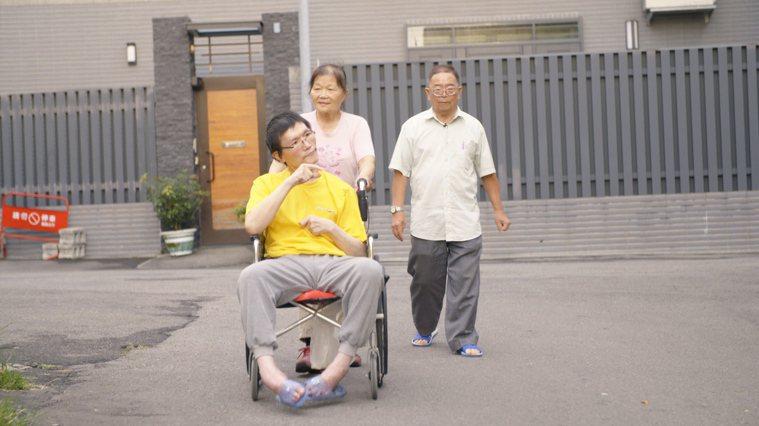 採訪這天,張國寬心情好,母親推著坐在輪椅上的他,父親(右)緊跟在兩人身後,一起散...