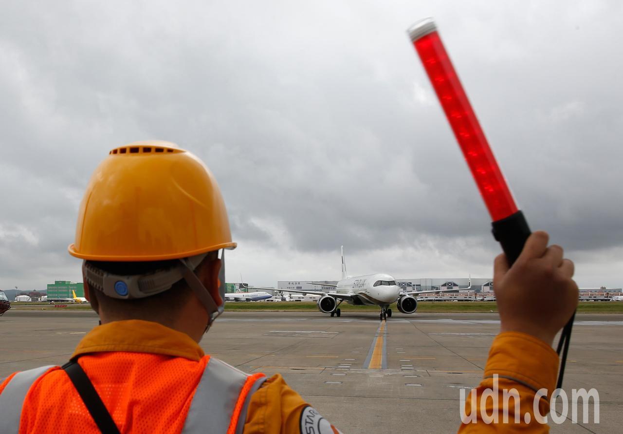 星宇航空第一架飛機中午降落在桃園機場,地勤人員引導飛機停妥。記者鄭超文/攝影