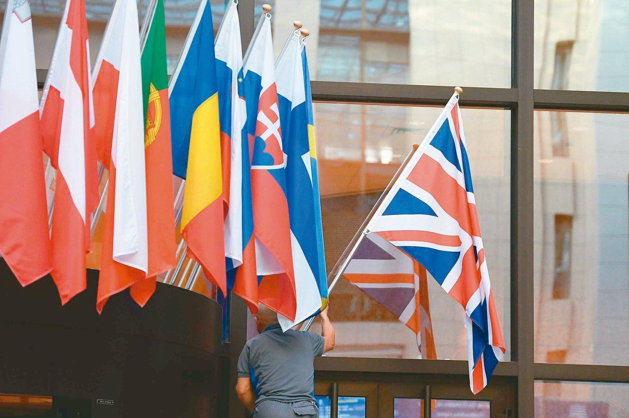 一名工作人員廿八日在歐盟總部門口插上英國國旗。 (法新社)