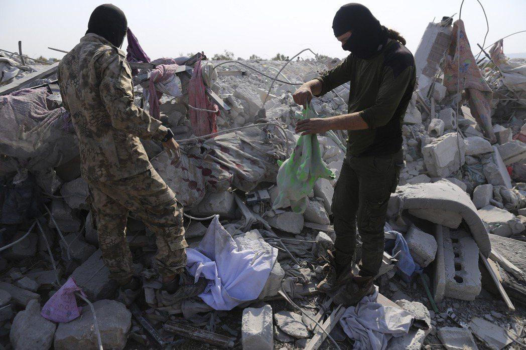 美軍突襲巴格達迪後將他藏身之處夷為平地,當地一些民兵27日在現場檢視。(美聯社)