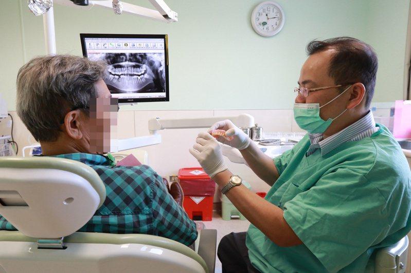 亞洲大學附屬醫院牙科主任廖明德(右)說,吸附性全口活動假牙,不僅假牙與牙床密合度佳,也方便平時清潔假牙。圖/亞洲大學附屬醫院提供