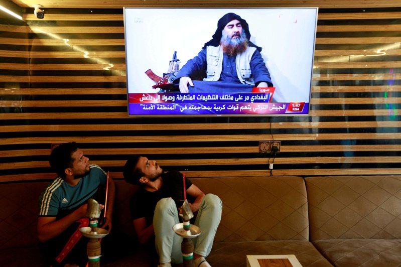 兩名伊拉克青年看著電視報導巴格達迪的死訊。(路透)