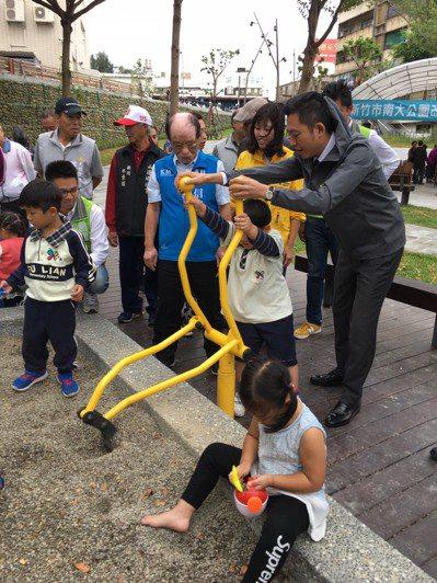 市長林智堅(右一)與小朋友玩共融遊具碎石坑的挖土機。 記者王駿杰/攝影